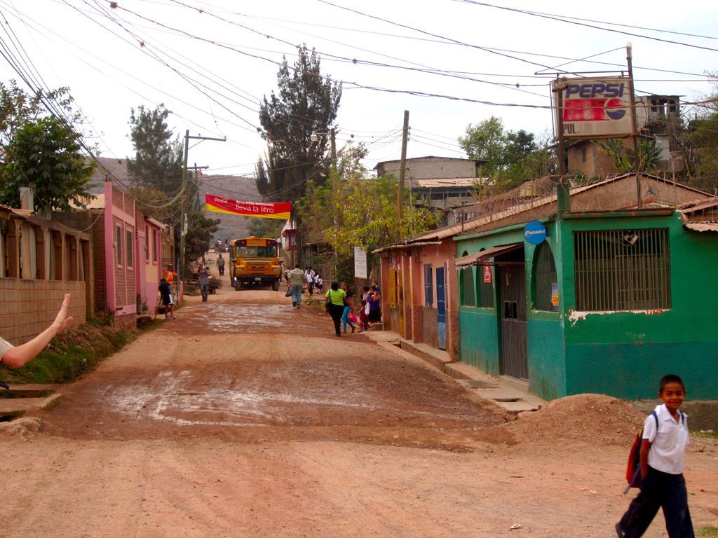 En tonstung skolebus kommer kørende i slumkvarteret. Bag rattet sidder en blot 12-årig dreng og smiler bredt!