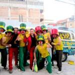 Næsefest og gule hænder. Showet blev en succes og her er hovedpersonerne fotograferet med det deltagende sambaorkester. Et kontrastfyldt øjeblik hvor smil mødte frygt, for i baggrunden ses en af de udstationerede politibetjente med automatvåben og skudsikker vest.