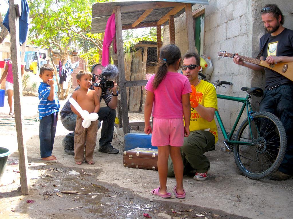 """Tilfældigt besøg og improviseret lille """"mini-show"""" i en baggård. Martin med kamera, Thomas med guitar og Jesper med ballondyr. Der er ikke noget at sige til, at børnene måber."""